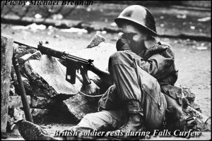 A weary British soldier sits amid the rubble of days of rioting in Belfast.
